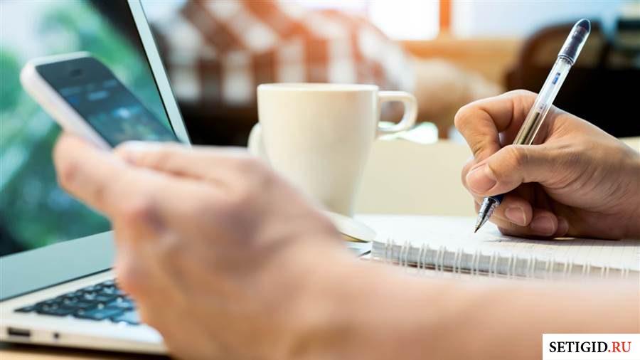 Мобильный телефон в руках и ручка перед ноутбуком5c5b43e294640