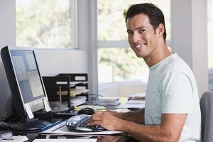 Man in home office using computer and smiling5cb82b5399298